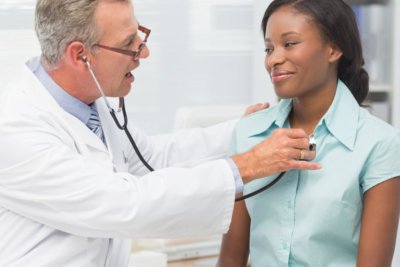 doctor listening to cheerful patients chest with stethoscope