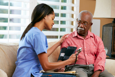 a young lady getting blood pressure of the old man
